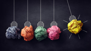 Newtons cradle crumpled paper bulb bright idea on blackboard